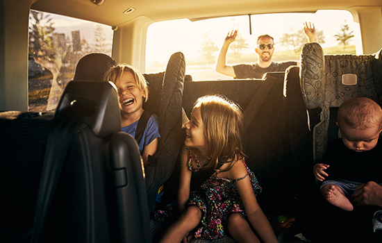 Features Image - family in car with hands raised in joy